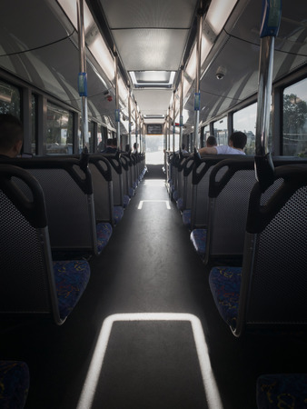 Inside the top deck of a bus during the day, with passengers. Looking down the aisle