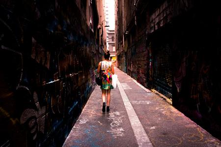 A woman walking down an grungy urban inner city laneway with shopping bags. Dark.