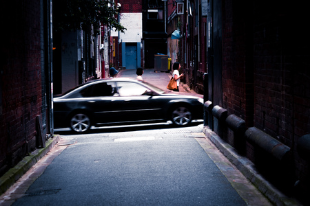 People and a car travelling up a small road. Urban laneway.