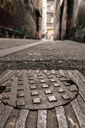 Close up of a street drain cover, looking up an urban laneway in a downtown city district. Grungy.