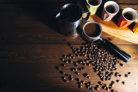 Dark food photography.Coffee beans, tamper, portafilter, grinds and espresso cups on a wooden surface. 版權商用圖片