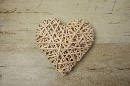 White wood wicker heart on the timber wooden background. Decorative. 免版税图像
