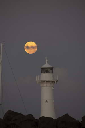 Moon Rising over the Wollongong Breakwater Lighthouse. Evening twilight.