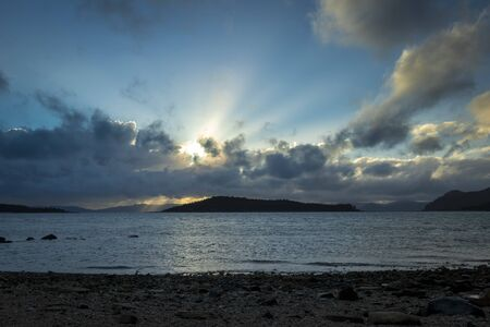 The sun is setting, rising amongst the islands in the Whitsundays, which os located off the coast of Queensland, Australia.