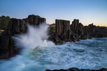 Bombo Quarry Headland, NSW, Australia. Morning sunrise with sea waves crashing onto the rugged coastline.