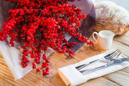 CHRISTMAS BOUQUET OF RED WINTERBERRY FLOWERS ON A WOODEN TABLE Stock Photo