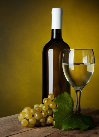 merlot: A glass full of wine and bottle on a yellow background