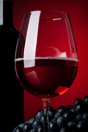 A glass full of wine and bottle on a red background photo