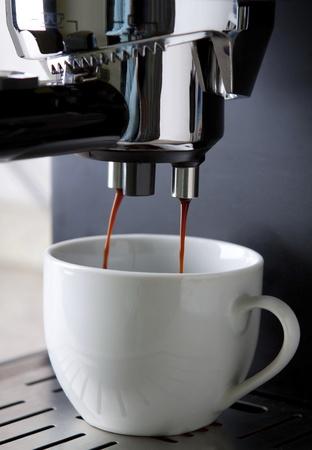 Cafetera para caf� expr�s en la acci�n con taza blanca