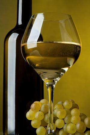 white wine glass: A glass of wine, bottle and grapes on a yellow background