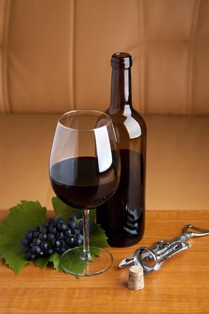Un vaso y una botella de vino tinto servido en la mesa