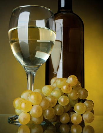 A glass of wine, bottle and grapes on a yellow background photo