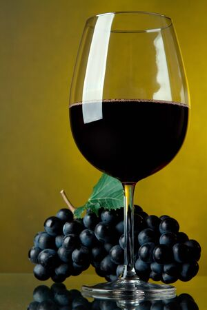 merlot: A glass of red wine and grapes on a yellow background