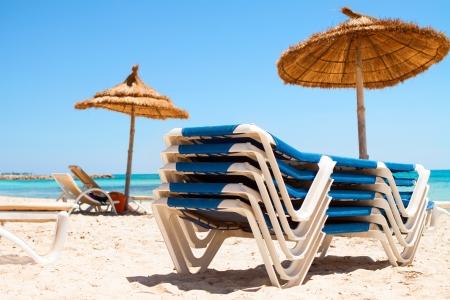 Tumbonas y sombrilla en una playa de arena