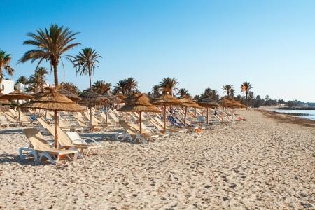 Playa de arena con tumbonas y sombrillas al atardecer Foto de archivo