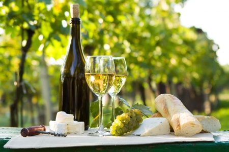 Two glasses of white wine, bottle, cheese and baguette