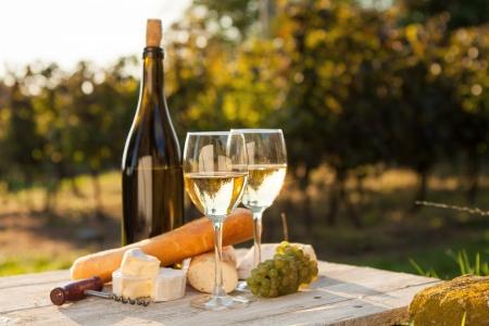 Dos vasos de vino blanco y una botella en la puesta del sol