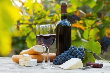 Dos vasos de vino rojo, botella, queso y baguette Foto de archivo