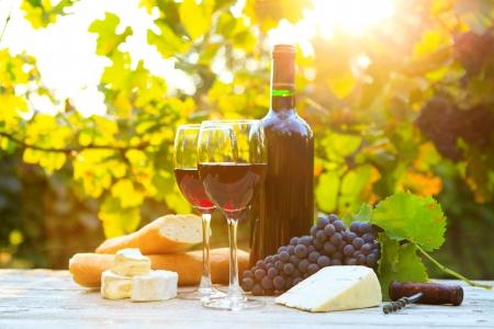 Twee glazen rode wijn, fles, kaas en stokbrood