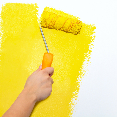 refit: Painting roller on white wall with yellow paint