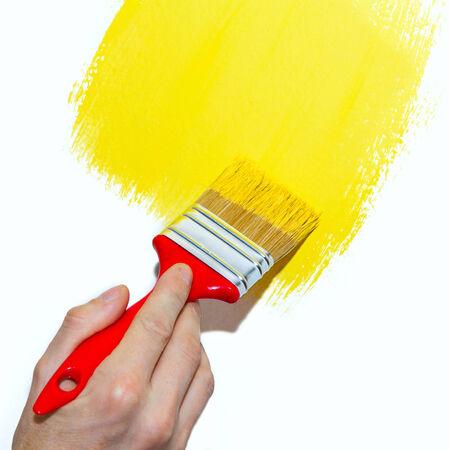 Cepillo de pintura en una pared amarilla blanca