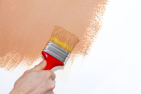 refit: Painting roller on white wall with brown paint