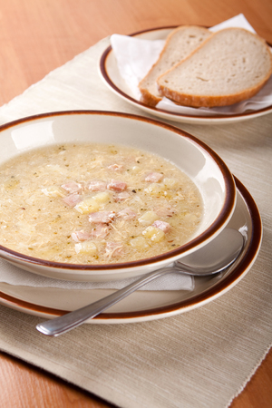 potato soup: Potato soup with sausage and bread on table
