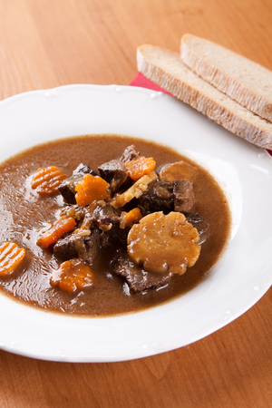 Beef goulash with fresh sliced mushrooms, oil and vegetables photo