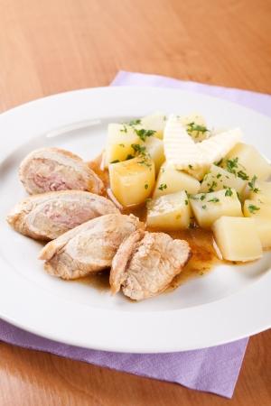 Rollos de carne de cerdo con chucrut y patatas cocidas en la mesa