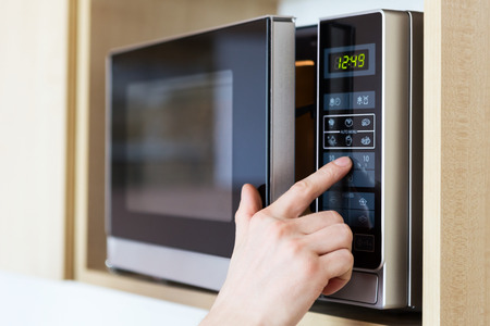 Détail de la main des hommes tout en utilisant le micro-ondes Banque d'images - 26717864