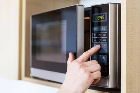 Detalle de la mano masculina cuando el microondas