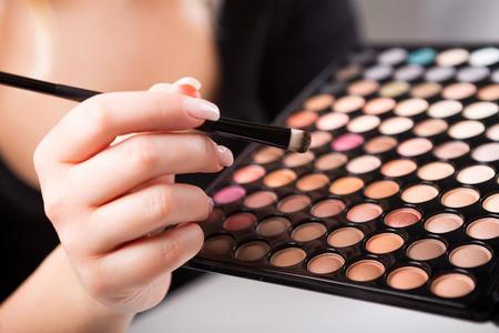 make up eyes: Female hand holding makeup brush and paints