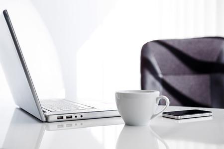 Lugar de trabajo con ordenador portátil abierto, teléfono móvil y una taza de café Foto de archivo