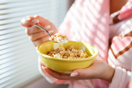 bowl of cereal: A close up shot of a woman holding a bowl of cereal and a raised spoon of cereal