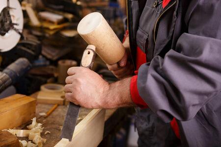 trinchante: Manos tallador en el trabajo con un martillo de madera y un cincel Foto de archivo