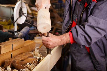 schnitzer: H�nde Schnitzer bei der Arbeit mit einem Holzhammer und Mei�el