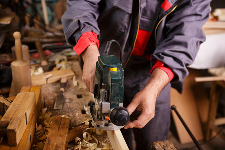 joinery: The carpenter hands when working with electric planer joinery