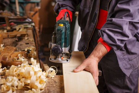 The carpenter hands when working with electric planer joinery photo
