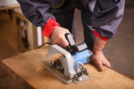 Manos carpintero que trabaja con la sierra circular