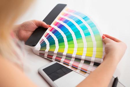 Diseñador gráfico que trabaja en una tableta digital en el fondo con la paleta pantone