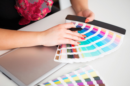 Graphic designer working on a digital tablet in the background with pantone palette photo