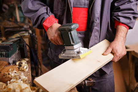 Carpenter at work with the sander on a wooden board photo