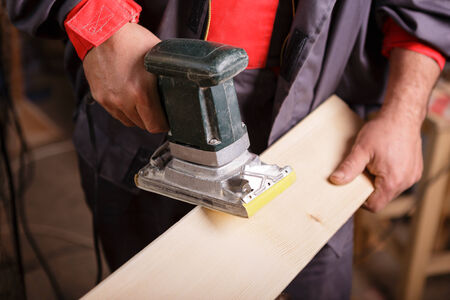 sander: Carpenter at work with the sander on a wooden board