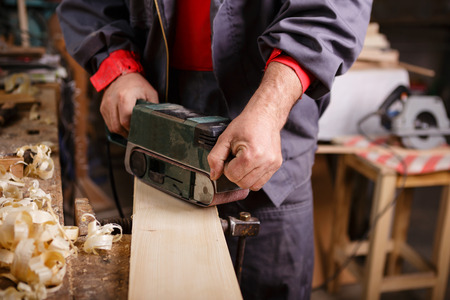 carpenter's sawdust: Joiner with a belt sander on a wooden board with sawdust
