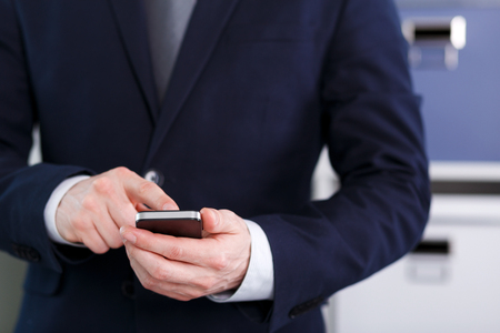 holding cell: Businessman holding a cell phone and writing sms message in office