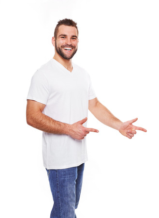 Happy young man in white tshirt showing empty copyspace on white background photo