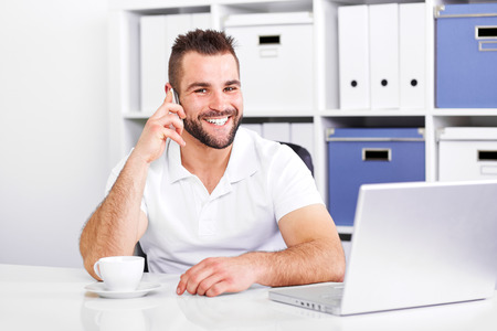 telephone salesman: Happy business man talking on the phone in office
