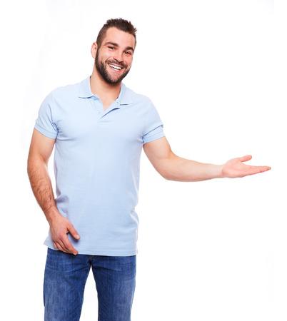 Feliz el hombre joven en camisa de polo que muestra el copyspace vac�o en el fondo blanco Foto de archivo