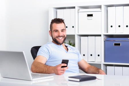 Young businessman holding a cell phone and writing sms message in office photo