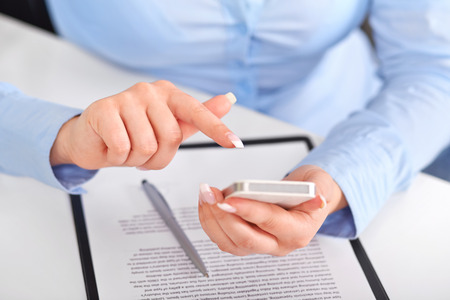 Young woman working with a mobile phone above the contract and pen photo